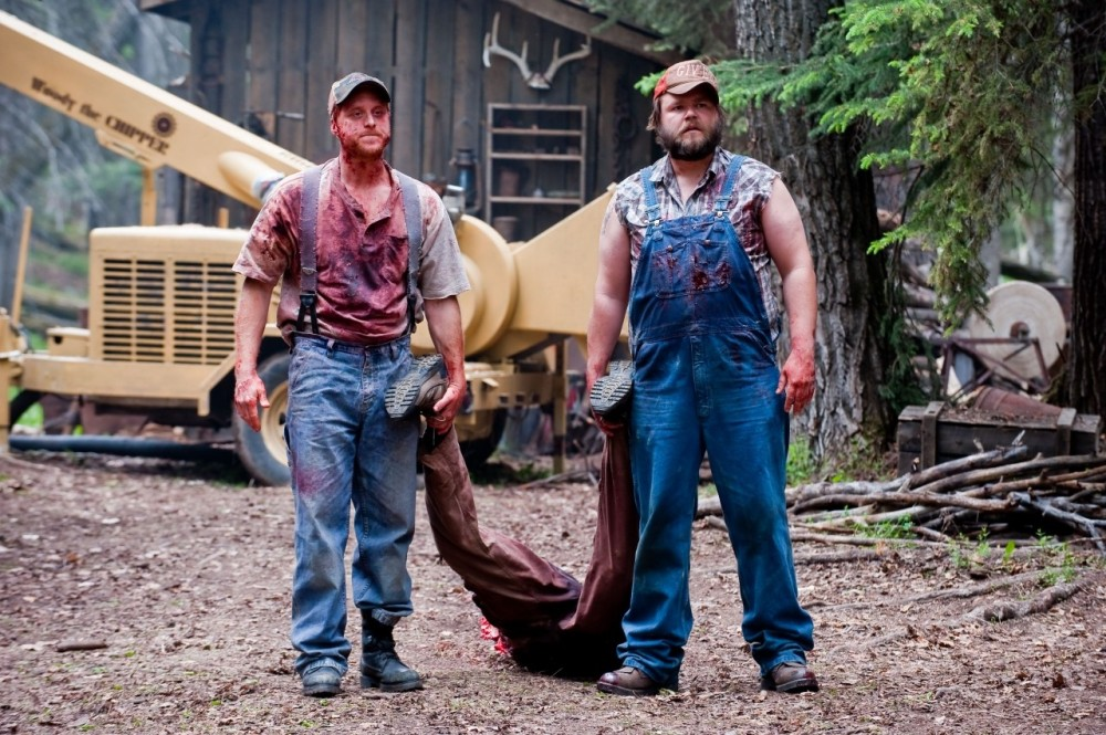 Tucker and Dale standing in front of the wood chipper holding onto the feet of half a guy